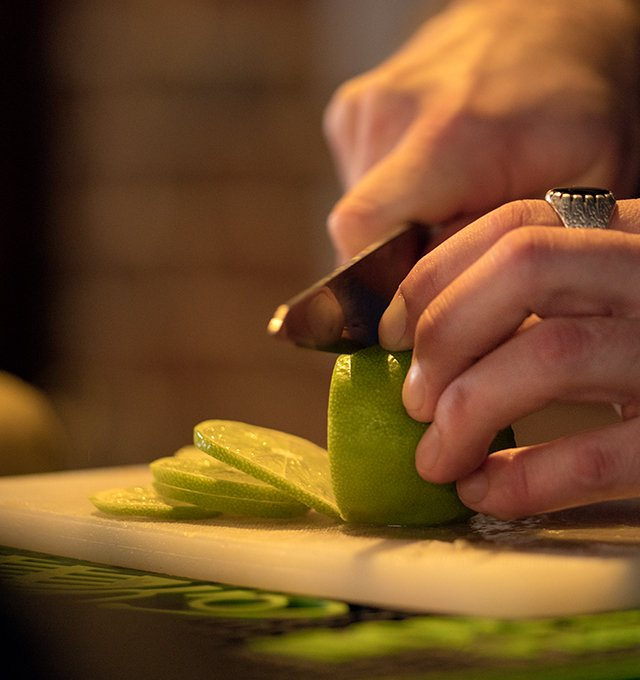 Fresh lime being sliced for drinks