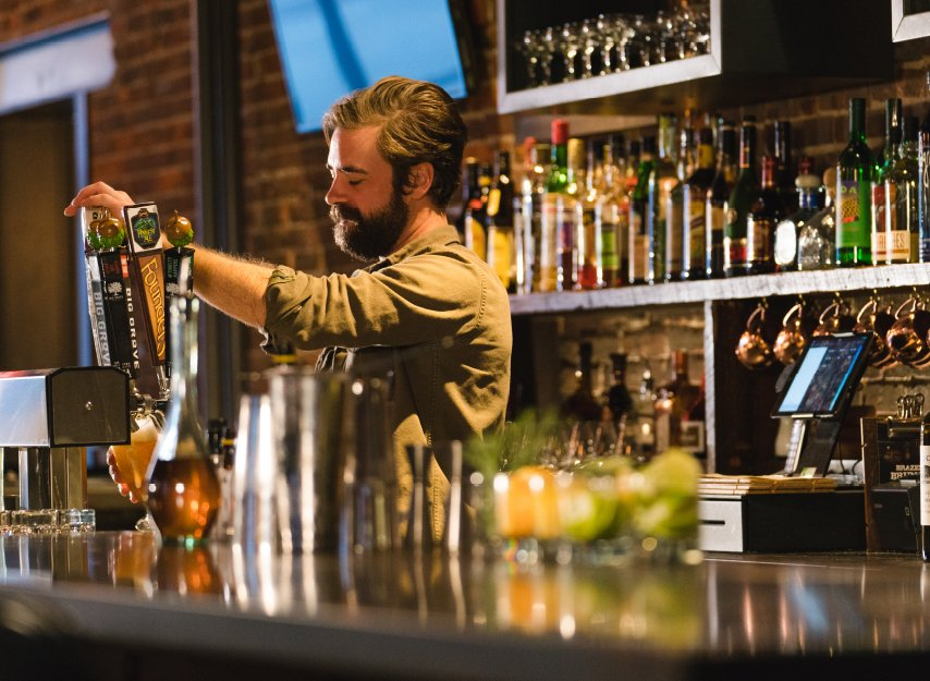 Photo of Bartender pouring a craft beer at Brazen Bar